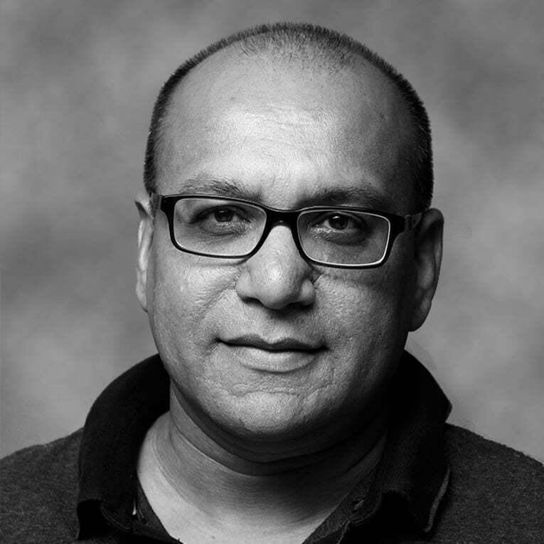 Ken Ramroochsingh, bald man, glasses, short hair, black and white filter